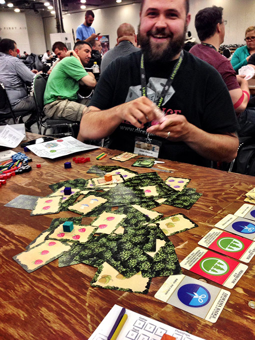 """Camp Khaki with designer Jason Kotarski. In the game, players are playing scouts on a retreat, trying to take pictures of nature and earn merit badges. There is a unique """"messy card"""" mechanic that is a ton of fun."""