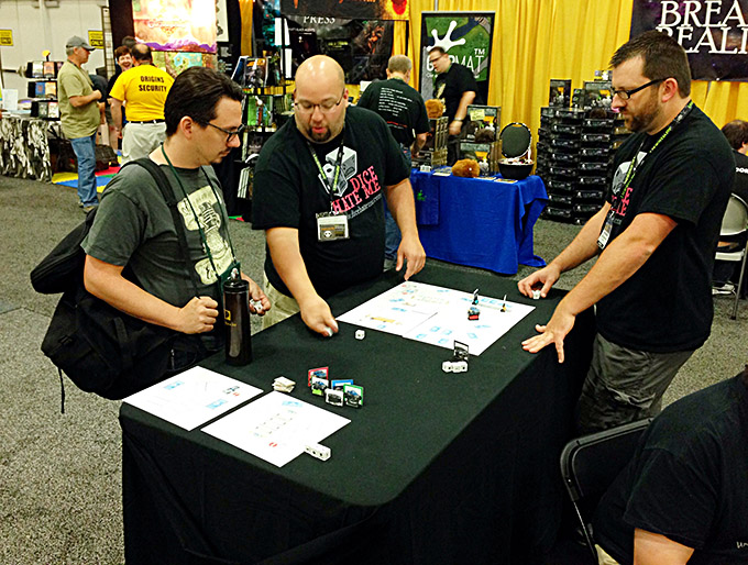 Matt Riddle and Ben Pinchback join the Dice Hate Me Games booth to show off their real-time dice-rolling racing game, Monster Truck Mayhem. Mayhem did, indeed, ensue and the game drew a big crowd to the booth. Look for Monster Truck Mayhem from Dice Hate Me Games in spring of 2015!