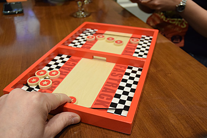 Fasttrack from Blue Orange Games! This classic dexterity game is the perfect bar game, and I highly recommend it for anyone's collection.
