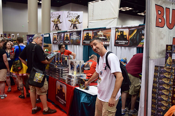Dan Patriss in front of the Stronghold Games booth (with Stephen Buonocore working his magic in the background).