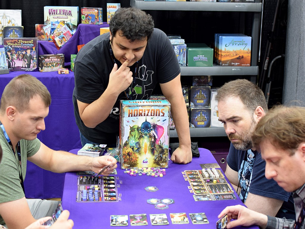 Isaias Vallejo showing off Levi Mote's newest design, Horizons, in the Daily Magic Games booth.
