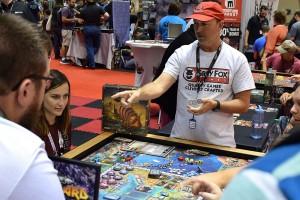 BJ Rozas teaching Reavers of Midgard in the Greyfox Games booth.